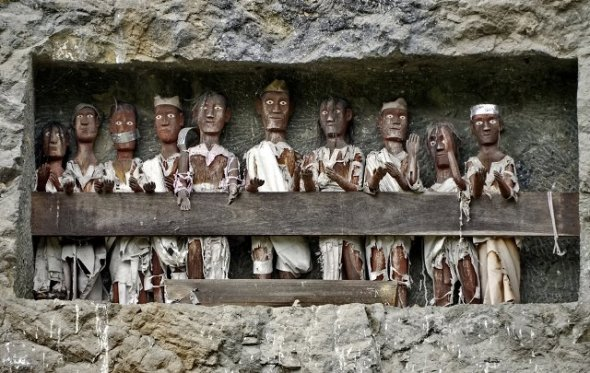 """One more interesting story of Tana Toraja tau tau where the technical term meaning a human statue as a representation of the person who died. The statue was placed in a stone cave carved balconies resembling residence. Inside the cave stone, the coffin of the late """"hidden"""" to avoid grave robbery. Tana Toraja is approximately 328 km and can be reached by land travel about 7-10 hours."""